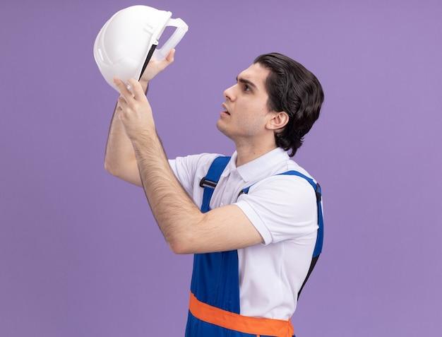 Молодой строитель в строительной форме держит свой защитный шлем и заинтригованно смотрит на него, стоя над фиолетовой стеной