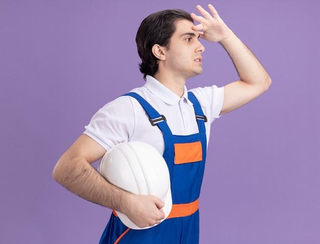 紫色の壁の上に立っている頭の上に手で遠くを見ている彼の安全ヘルメットを保持している建設制服の若いビルダー男