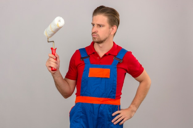 Молодой строитель мужчина в строительной форме, держа валик и скептически смотрит на него