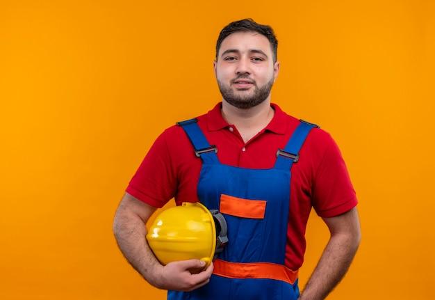 自信を持って笑顔でカメラを見ている安全ヘルメットを保持している建設制服の若いビルダー男