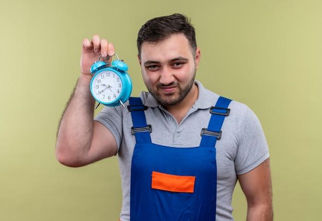 Молодой строитель человек в строительной форме показывает будильник, хитро глядя в камеру, улыбаясь