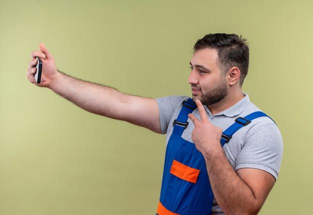 Молодой строитель в строительной форме делает селфи на своем смартфоне и показывает знак победы на камеру
