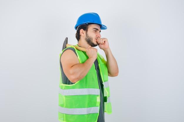 肩にハンマーを保持し、口に拳を保ち、物思いにふける、正面図を保持している作業服の制服を着た若いビルダーの男。
