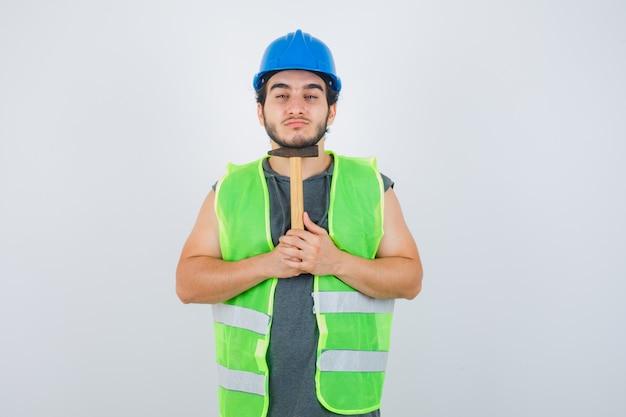 あごの下にハンマーを保持し、自信を持って見える作業服の制服を着た若いビルダーの男、正面図。