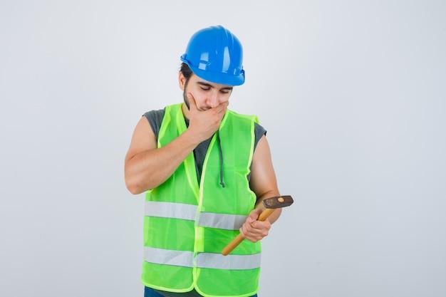 作業服の制服を着た若いビルダーの男は、口に手を保ち、思慮深く、正面図を見てハンマーを保持しています。