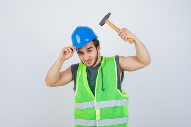 ヘルメットとハンマーを保持し、自信を持って、正面図を見て作業服の制服を着た若いビルダーの男。