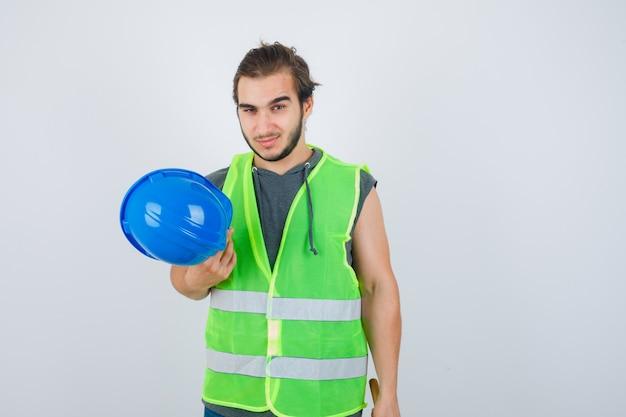 ヘルメットを保持し、自信を持って、正面図を探している作業服の制服を着た若いビルダーの男。