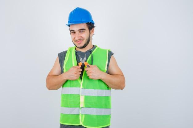 ペンチを保持し、陽気に見える作業服の制服を着た若いビルダーの男、正面図。