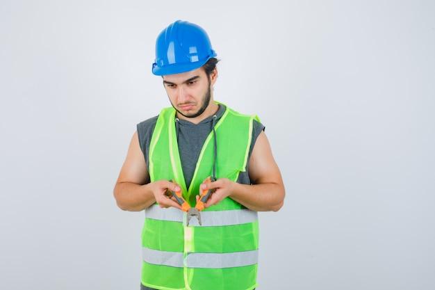 ペンチを保持し、物思いにふける、正面図を探している作業服の制服を着た若いビルダーの男。