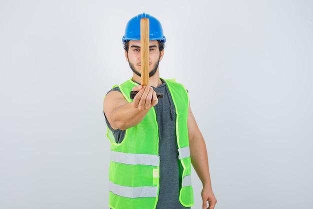 작업복 제복을 입은 젊은 작성기 남자 카메라를 향해 망치를 긁고 자신감, 전면보기를 찾고.