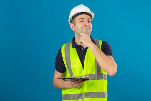흰색 헬멧과 파란색에 고립 된 클립 보드를 들고 노란색 조끼를 입고 꿈꾸는 얼굴에 젊은 작성기 남자