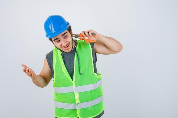 Uomo giovane costruttore pizzicando l'orecchio con le pinze in uniforme da lavoro e guardando divertito, vista frontale.