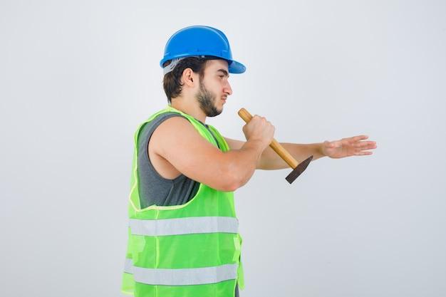 Uomo giovane costruttore remowing qualcosa con l'utilizzo di un martello in uniforme da lavoro e guardando fiducioso, vista frontale.
