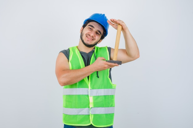 Young builder man showing hammer size in workwear uniform and looking cheery , front view.