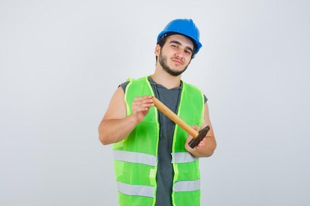Uomo del giovane costruttore che mostra martello in uniforme da lavoro e che sembra soddisfatto, vista frontale.