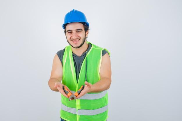 Uomo del giovane costruttore che mostra le pinze in uniforme da lavoro e che sembra gioioso, vista frontale.