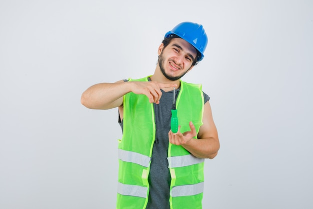 Young builder man in uniform showing size sign with screwdriver and looking happy , front view.