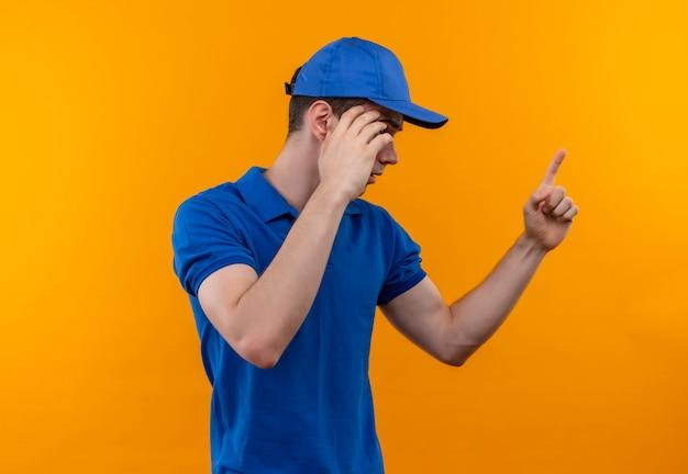 建設ユニフォームとキャップを身に着けている若いビルダーの男は指で何かを説明します