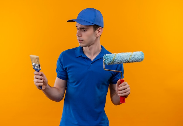 建設ユニフォームとキャップを身に着けている若いビルダーの男は、ペイントブラシとローラーブラシを保持します
