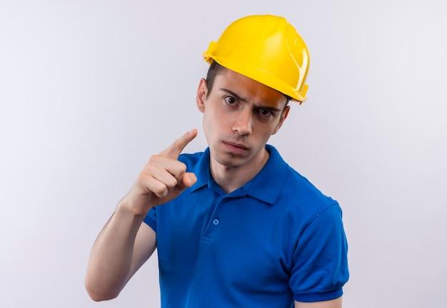 建設制服と安全ヘルメットを身に着けている若いビルダーの男は怒って誰かを非難します
