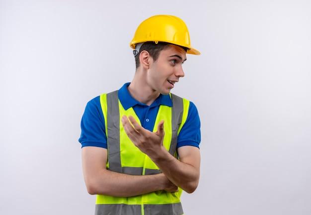 建設制服と安全ヘルメットを身に着けている若いビルダーの男が尋ねる