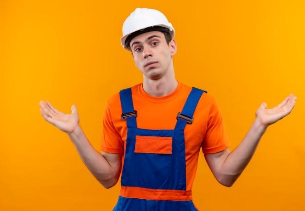 建設制服と安全ヘルメットを身に着けている若いビルダー男が混乱