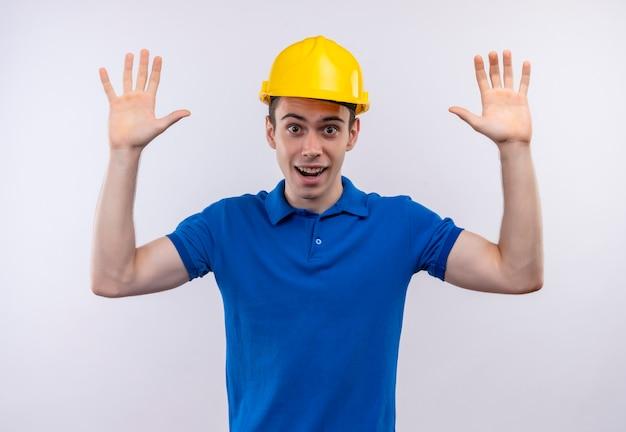 建設制服と安全ヘルメットを身に着けている若いビルダーの男は幸せな腕を上げています