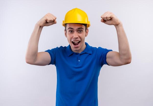 幸せな拳をやっている建設制服と安全ヘルメットを身に着けている若いビルダー男
