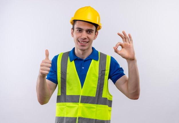 建設ユニフォームと安全ヘルメットを身に着けている若いビルダーの男は幸せな親指を上げてクール
