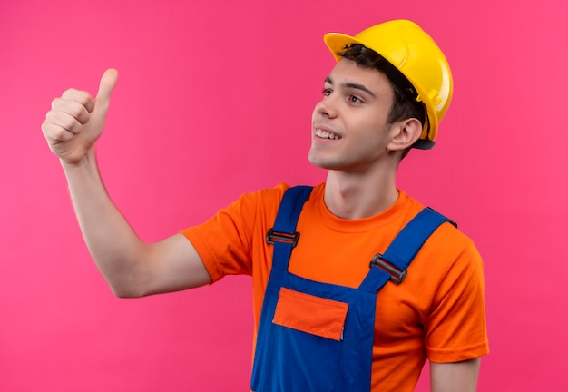 建設制服と安全ヘルメットを身に着けている若いビルダーの男は幸せな親指を立てる