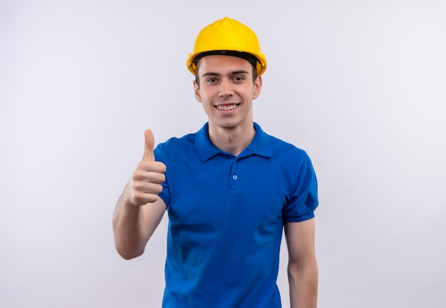 Молодой строитель человек в строительной форме и защитном шлеме делает счастливые пальцы вверх