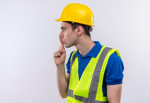 建設ユニフォームと安全ヘルメットを身に着けている若いビルダーの男は指で沈黙のジェスチャーをしています