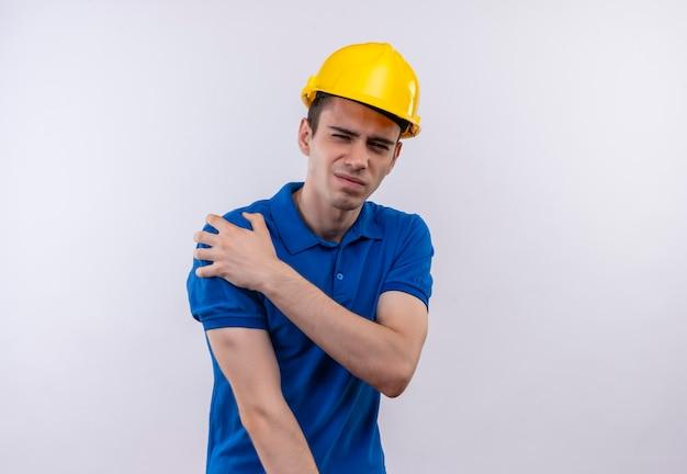 건설 유니폼 및 안전 헬멧을 착용하는 젊은 작성기 남자 불행한 얼굴을하고 고통을 앓고