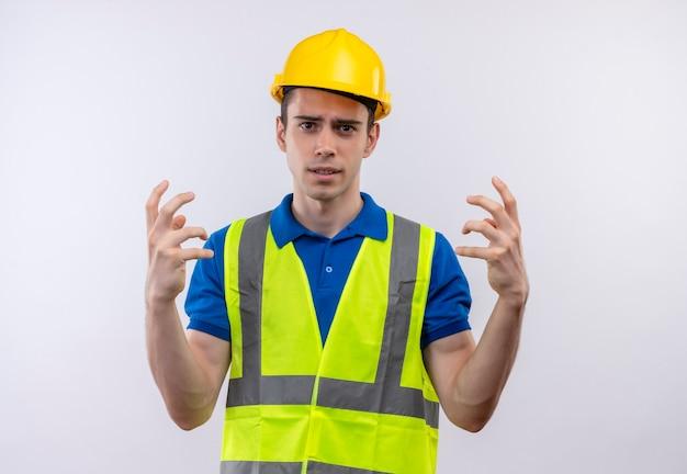 Молодой строитель человек в строительной форме и защитном шлеме пресытился