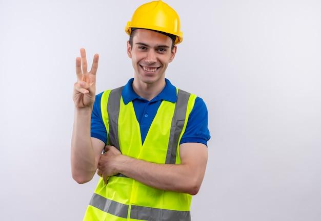 건설 유니폼과 안전 헬멧을 착용하는 젊은 작성기 남자는 행복하게 세 손가락을 보여줍니다