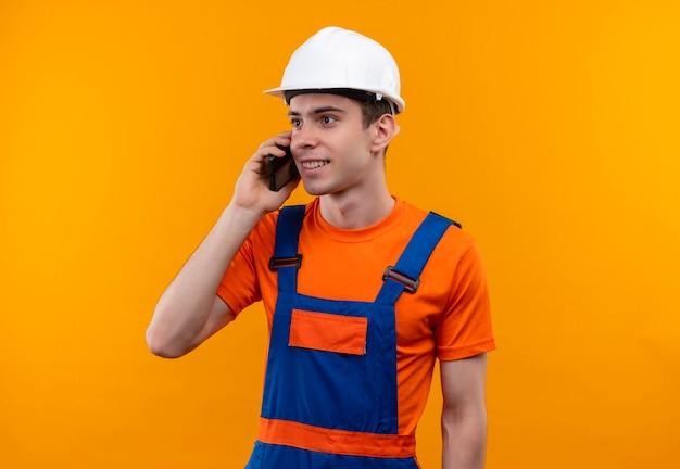 建設制服と安全ヘルメットを身に着けている若いビルダーの男が電話で楽しく話します
