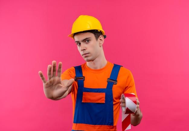 建設ユニフォームと安全ヘルメットを身に着けている若いビルダーの男は、赤白の信号を保持し、彼の手で停止を示しています