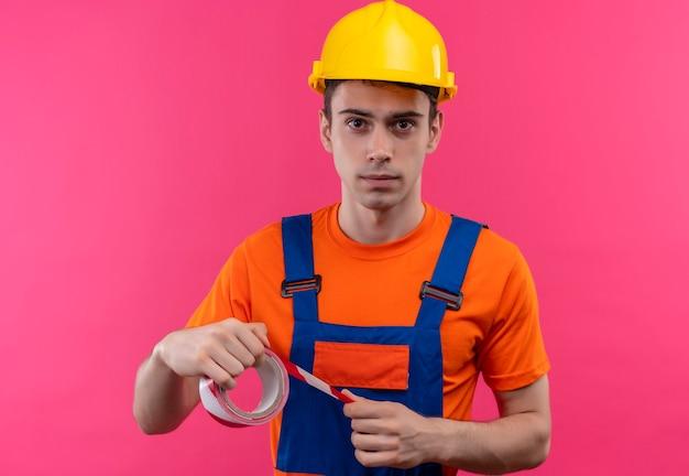 Молодой строитель в строительной форме и защитном шлеме держит кого-то красно-белую сигнальную ленту