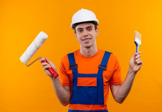 建設ユニフォームと安全ヘルメットを身に着けている若いビルダーの男はローラーブラシと壁のペイントブラシを保持します