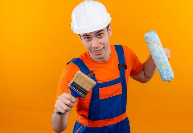 Молодой строитель в строительной форме и защитном шлеме держит валик и настенную малярную кисть