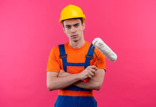建設制服と安全ヘルメットを身に着けている若いビルダーの男はローラーブラシを保持します