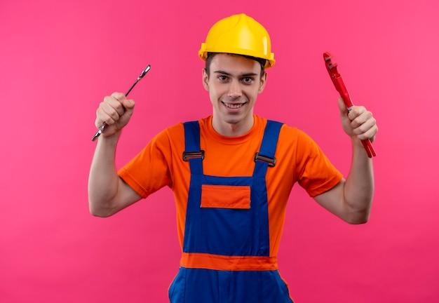 건설 유니폼과 안전 헬멧을 착용하는 젊은 작성기 남자는 렌치와 홈 플라이어를 보유하고