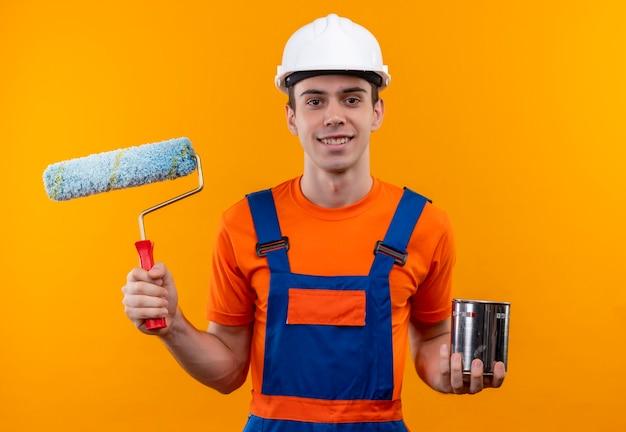 Молодой строитель в строительной форме и защитном шлеме держит валиковую кисть и контейнер с краской
