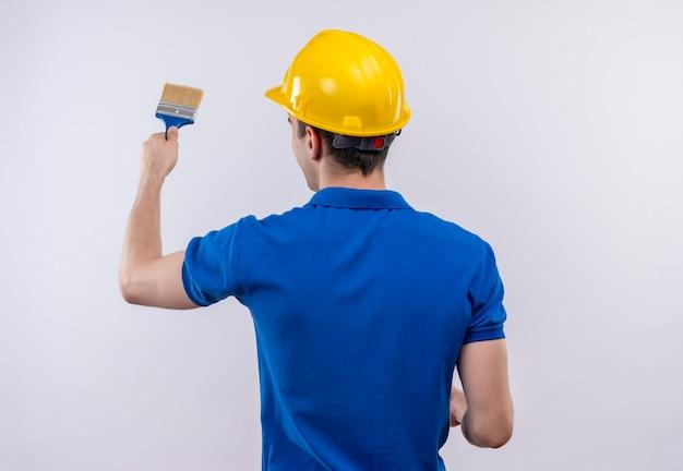 建設ユニフォームと安全ヘルメットを身に着けている若いビルダーの男はペイントブラシで壁をペイントします