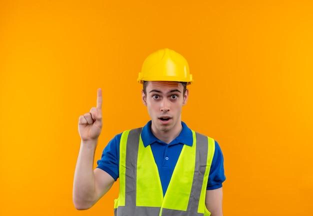 建設制服と安全ヘルメットを身に着けている若いビルダーの男は驚いて指で上向き
