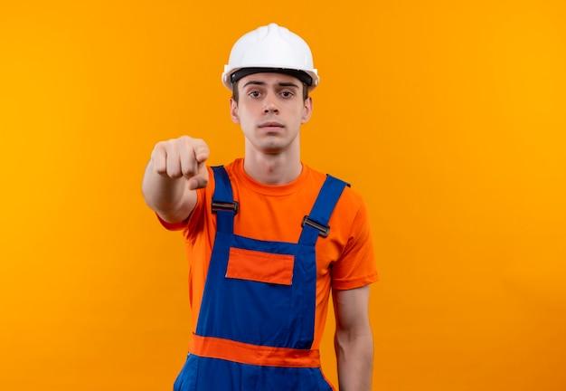 Молодой строитель человек в строительной форме и защитный шлем указывает пальцем