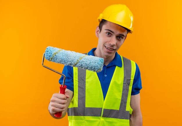 建設制服と安全ヘルメットを身に着けている若いビルダーの男は微笑んでローラーブラシを保持します