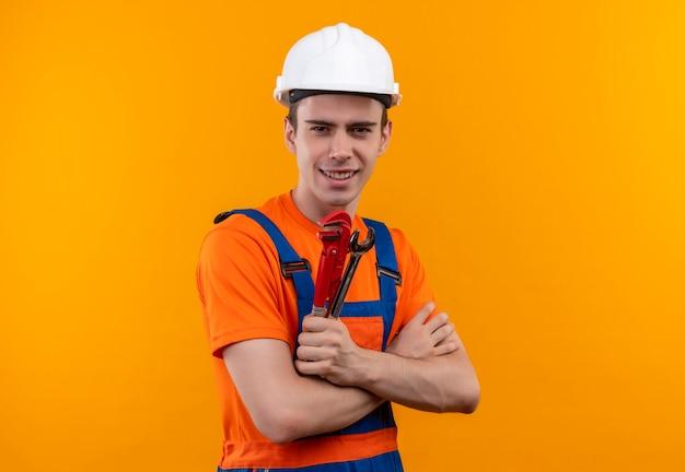건설 유니폼 및 안전 헬멧을 착용하는 젊은 작성기 남자는 미소를 짓고 그루브 펜치를 보유하고 있습니다.