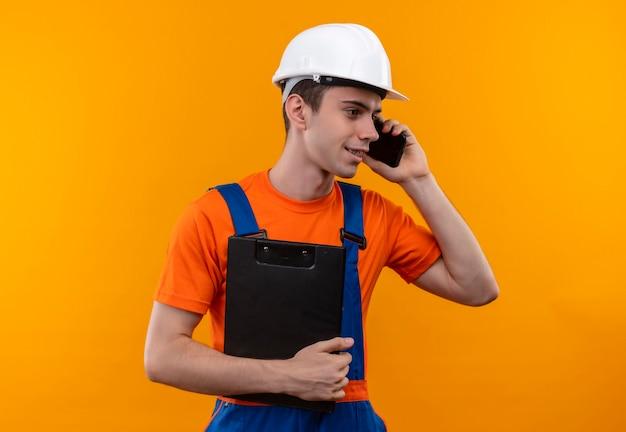 建設制服と安全ヘルメットを身に着けている若いビルダーの男が電話で話し、クリップボードを保持します