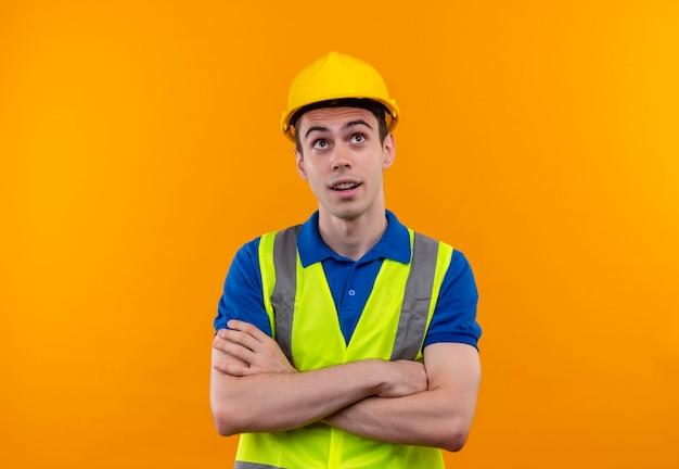 建設の制服と安全ヘルメットを身に着けて、考えて見上げる若いビルダー男